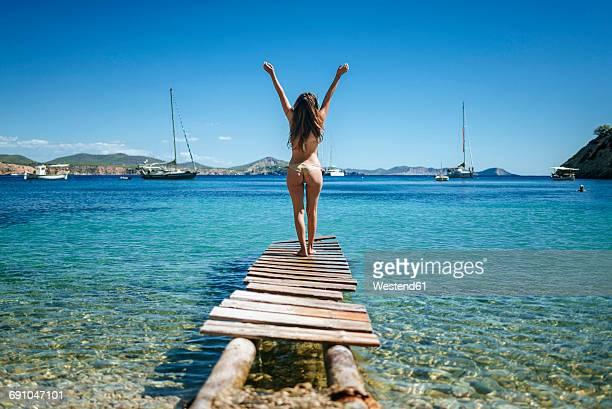Spian, Ibiza, Woman in bikini standing on jetty, rear view