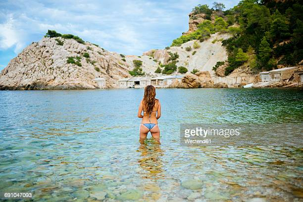 Spian, Ibiza, Woman standing in water at Llentrisca bieach