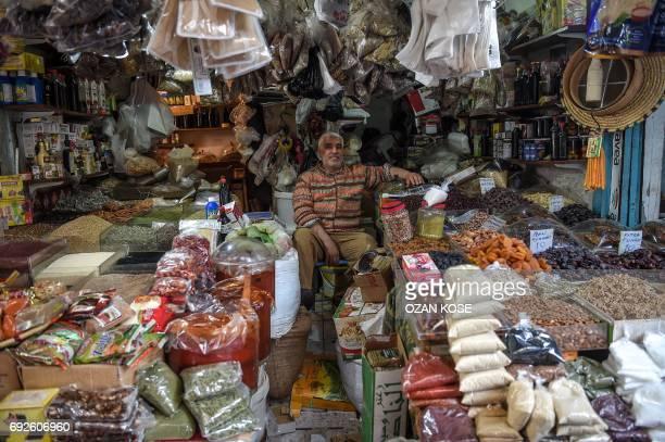 A spice seller waits his customers at his shop at the Antakya historical bazaar on June 5 2017 in Hatay / AFP PHOTO / OZAN KOSE