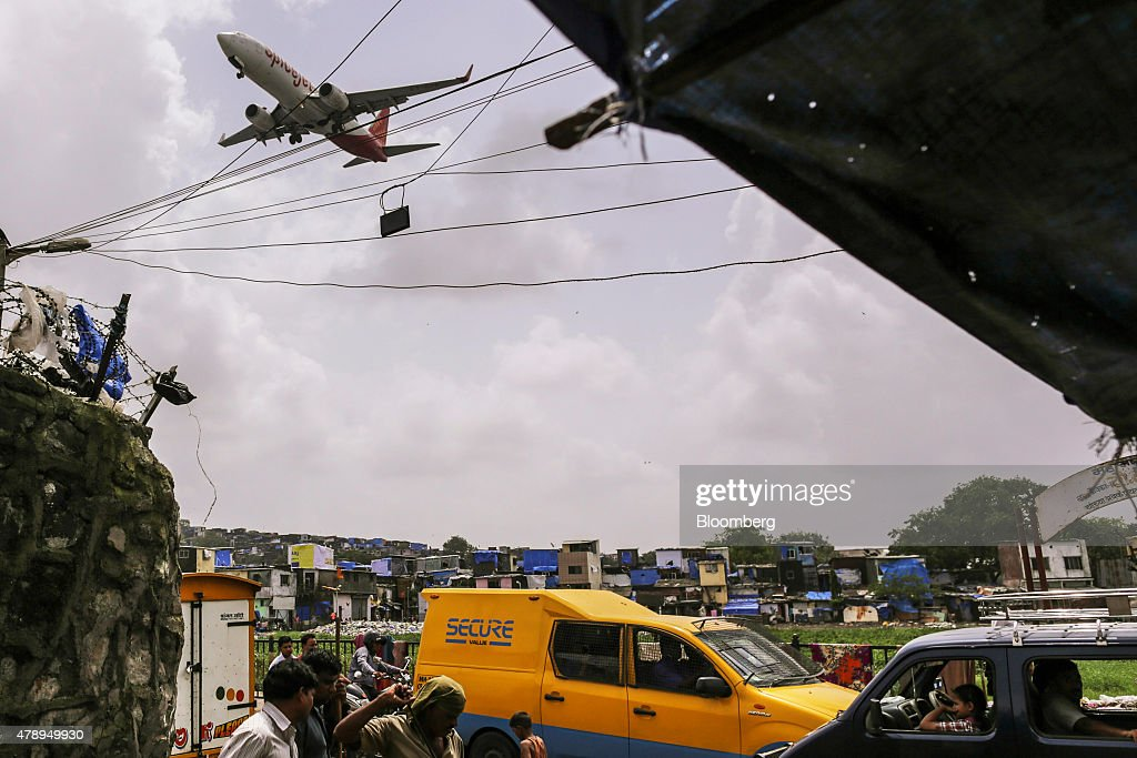A SpiceJet Ltd. aircraft flies over slum housing and pedestrians as it approaches to land at Chhatrapati Shivaji International Airport in Mumbai, India, on Saturday, June 27, 2015. Spice Jet is India's fourth biggest airline by market share according to the Indian Aviation Ministry. Photographer: Dhiraj Singh/Bloomberg via Getty Images