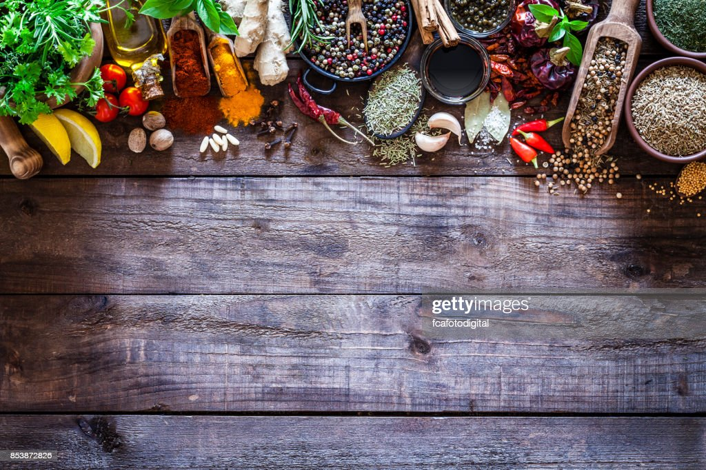Spices and herbs border on rustic wood kitchen table : Stock Photo