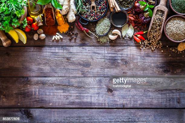 Spices and herbs border on rustic wood kitchen table