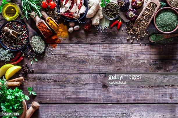 spices and herbs border on rustic wood kitchen table - indian food stock photos and pictures