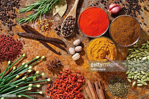 Spices and herbs displayed on rustic background shot from above