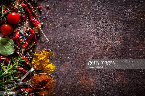 spices and herbs frame shot from above on rustic brown table - indian food stock pictures, royalty-free photos & images