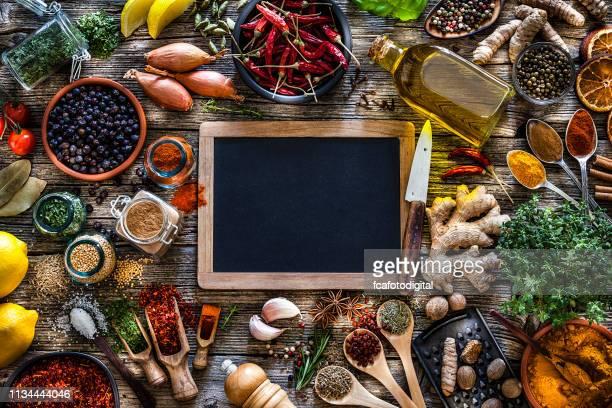 o frame das especiarias e das ervas disparou de acima na tabela de madeira rústica - receita - fotografias e filmes do acervo