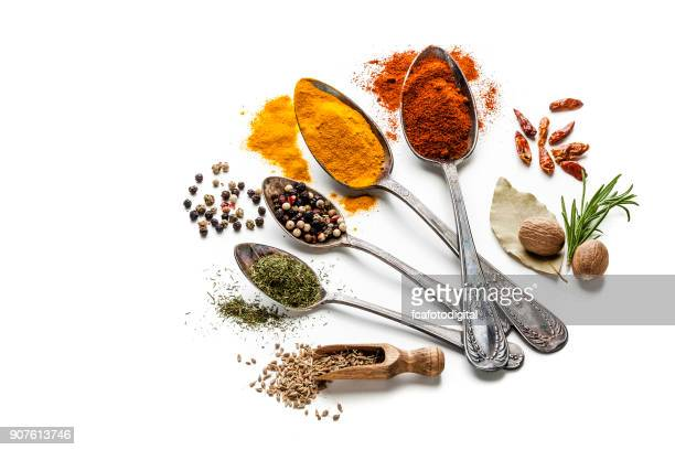 Spices and herbs in old spoons isolated on white background