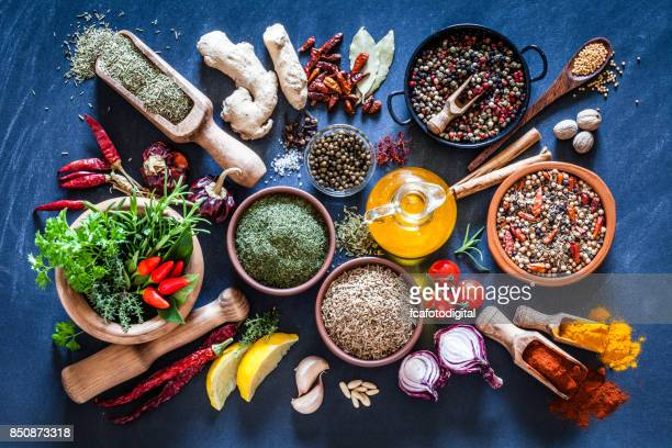 spices and herbs on dark bluish kitchen table - indian food stock photos and pictures