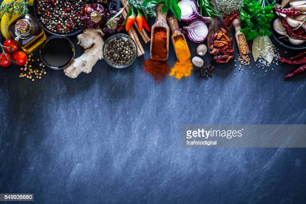 spices and herbs on dark kitchen table - curry powder stock photos and pictures