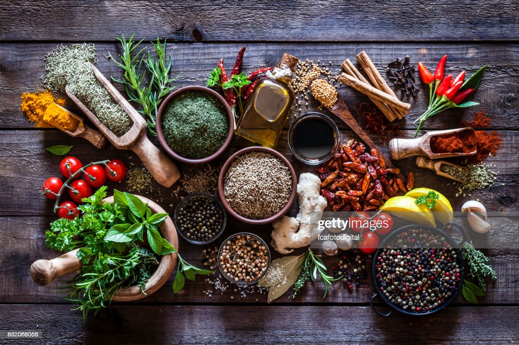Spices and herbs on rustic wood kitchen table : Stock Photo