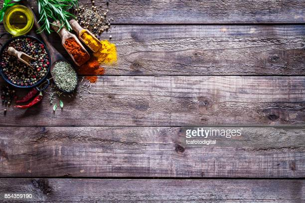 spices and herbs on rustic wood kitchen table - chili stock photos and pictures