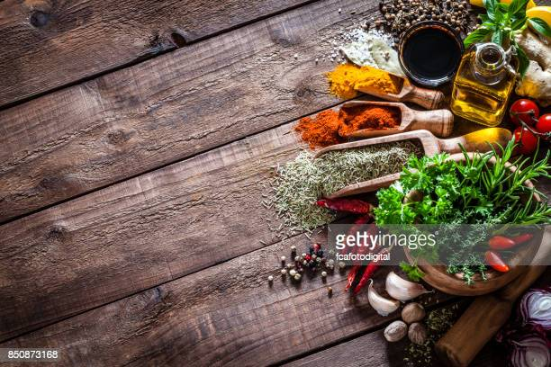spices and herbs on wooden kitchen table - kitchen background stock pictures, royalty-free photos & images