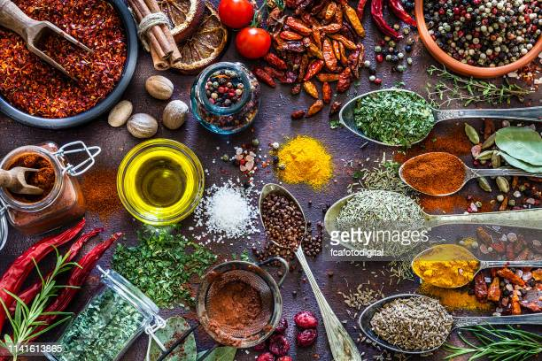 spices and herbs shot from above on rustic brown table - curry powder stock photos and pictures