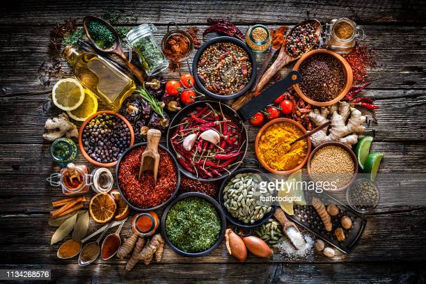 spices and herbs shot from above on rustic wooden table - indian food stock pictures, royalty-free photos & images