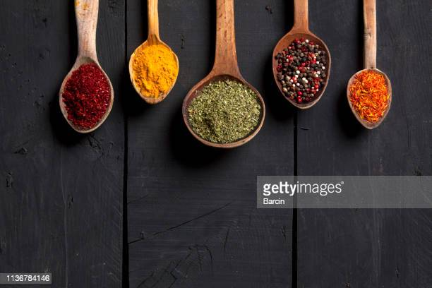 spices and herbs with old wooden spoons on wooden background - ingredient stock pictures, royalty-free photos & images