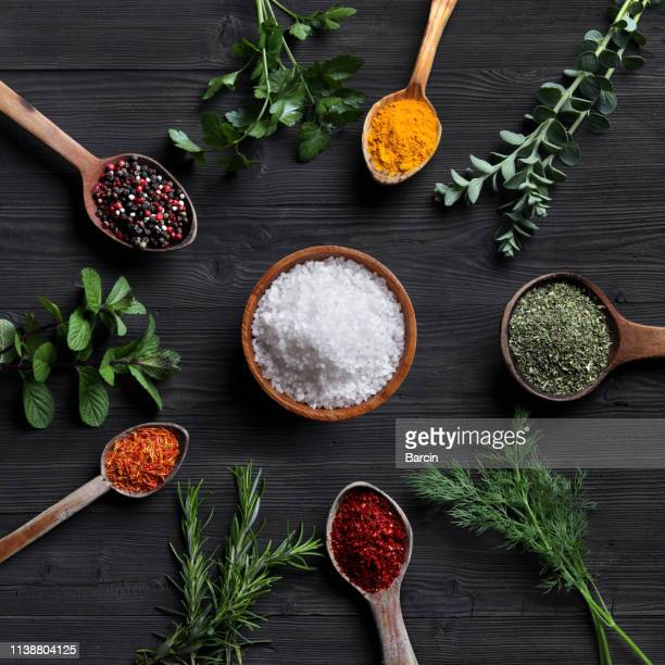 spices and herbs with old wooden spoons on wooden background - crushed leaves stock pictures, royalty-free photos & images