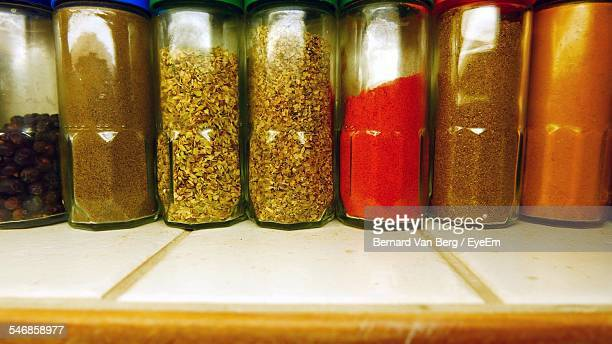 Spices In Glass Bottles Arranged On Counter
