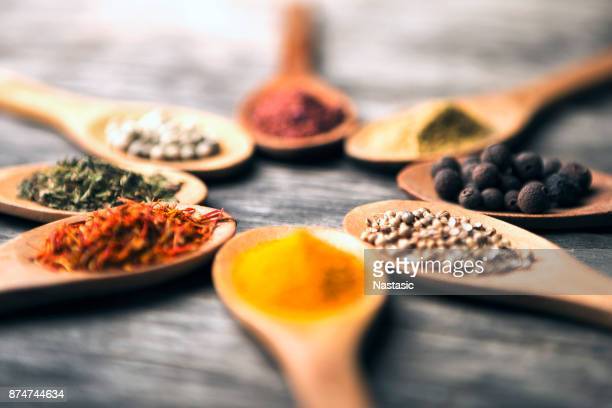 Spices in spoons arranged in circle