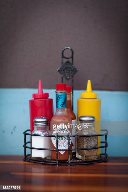 Spices ketchup and mustard containers are lined up at a fast foodrestaurant