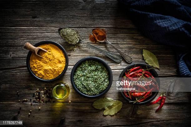 specerijen: kurkuma, chili pepers en gedroogde peterselie geschoten van bovenaf - drie dingen stockfoto's en -beelden