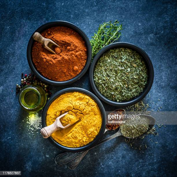 spices: turmeric, chili powder and dried parsley shot from above - spice stock pictures, royalty-free photos & images