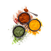 Spices: Turmeric, pepper powder and dried parsley shot from above on white background