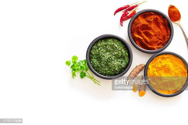 spices: turmeric, pepper powder and dried parsley shot from above on white background - spice stock pictures, royalty-free photos & images