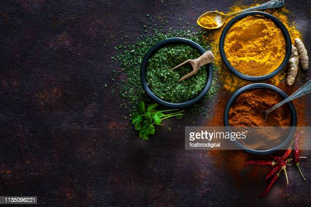 spices: turmeric, pepper powder and dried parsley shot from above - season stock pictures, royalty-free photos & images