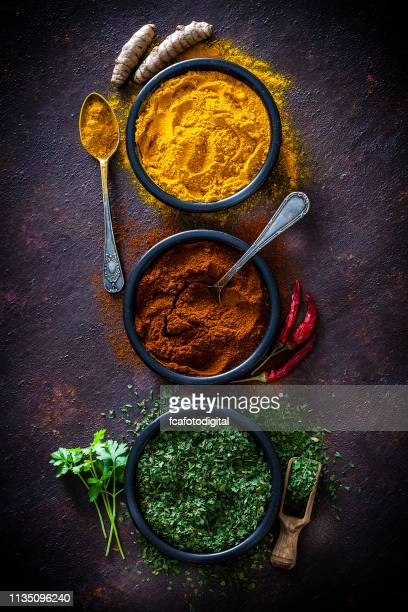 spices: turmeric, pepper powder and dried parsley shot from above - spice stock pictures, royalty-free photos & images