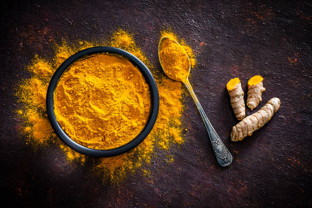 spices: turmeric roots and powder shot from above - turmeric stock pictures, royalty-free photos & images