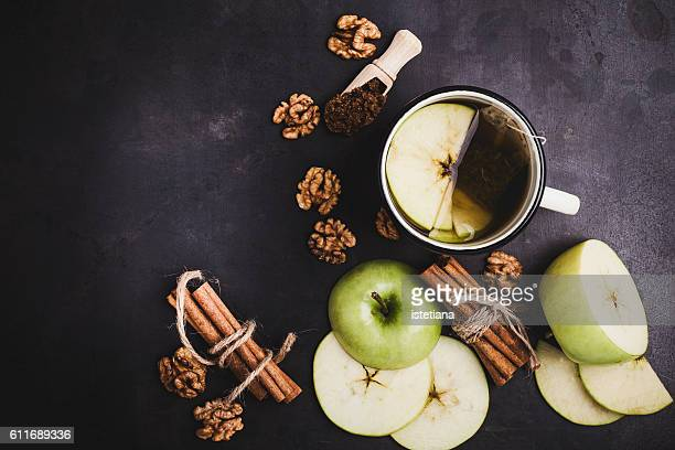 Spicy green tea with cinnamon and apple over rustic table viewed from above