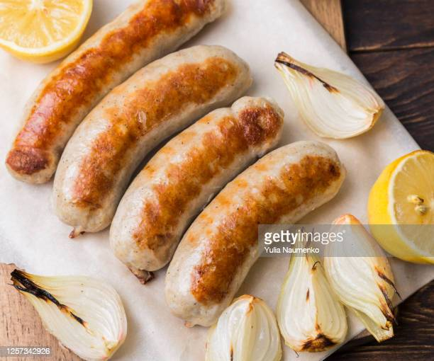 spicy homemade baked sausages with baked vegetables and spices on a brown wooden background. - sausage stock pictures, royalty-free photos & images