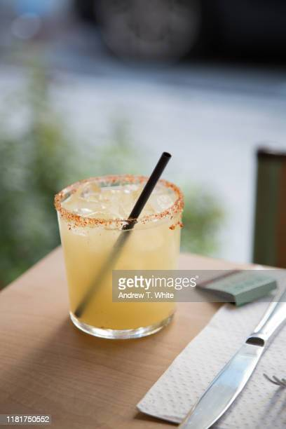 a spicy margarita sits on the edge of a table with street in background - vertical - margarita stock pictures, royalty-free photos & images