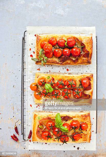 Spicy puff pastry pies stuffed with roasted tomatoes ant prosciutto
