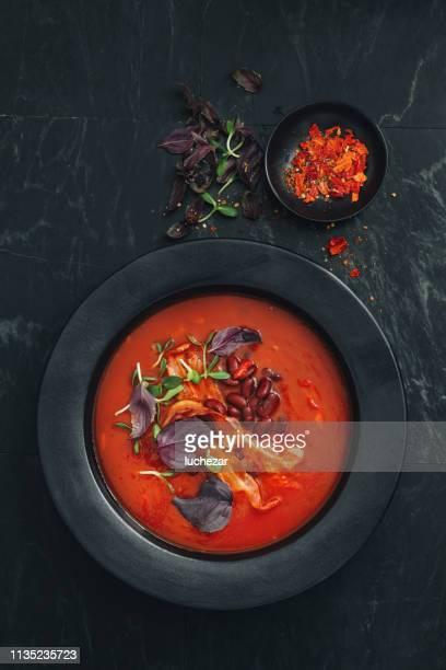 sopa picante do tomate, do feijão, da erva e do bacon fritado - pimenta em pó - fotografias e filmes do acervo