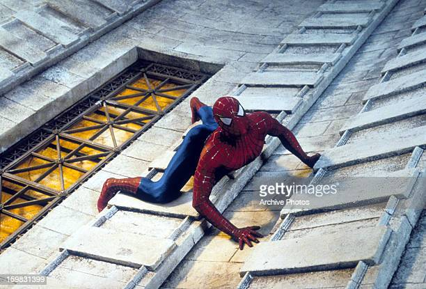 Spiderman climbing a tall building in a scene from the film 'Spiderman' 2002