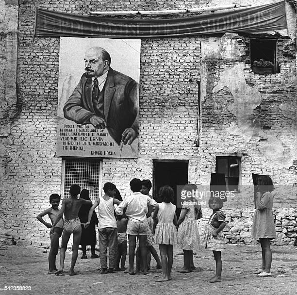 Spielende Kinder im Slumviertel von Durres unter LeninBild mit HoxhaParolen 1967