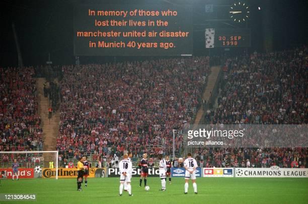 Spieler und Fans des englischen Fussballvereins Manchester United und des deutschen Fußballvereins FC Bayern München erheben sich am vor Beginn der...