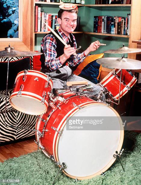 Spike Jones wears a comically small hat as he plays the drums.