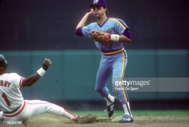 Spike Owen of the Seattle Mariners looks to throw to first base over the top of Al Bumbry of the Baltimore Orioles during a Major League Baseball...