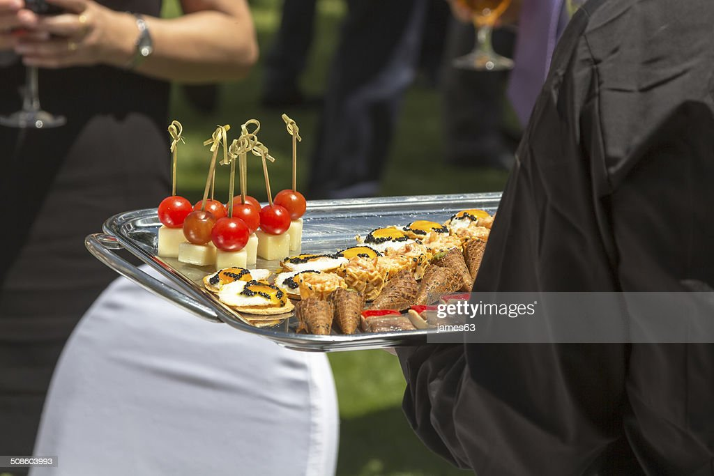 spiked cocktail and finger food snacks : Stock Photo