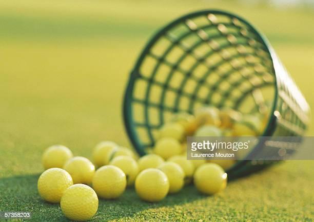 Spilled basket of yellow golf balls, close-up