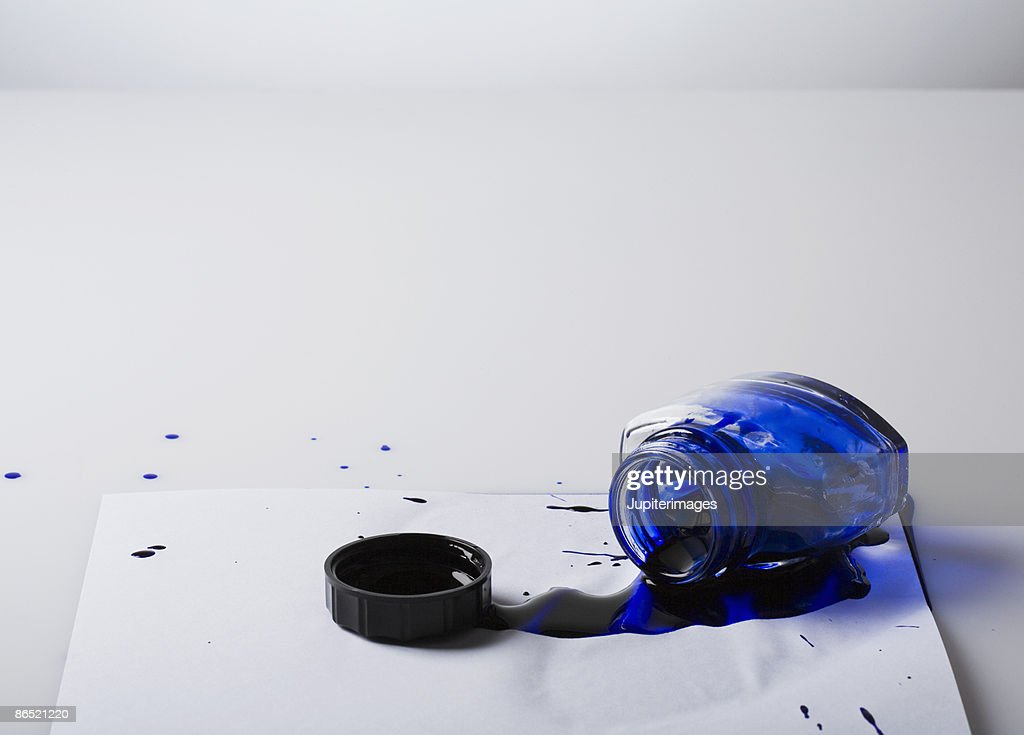 Spilled bottle of blue ink on paper : Stock Photo