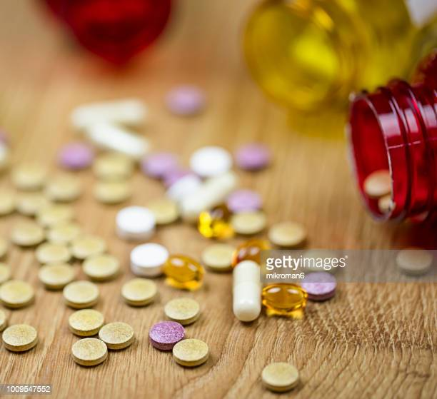 spilled capsules from prescription bottle on black background. medical concept - sexually transmitted disease stock photos and pictures
