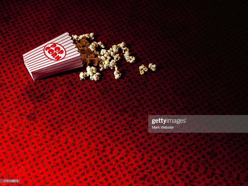 Spilled carton of popcorn on cinema carpet : Stock Photo
