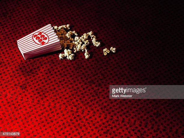 Spilled carton of popcorn on cinema carpet