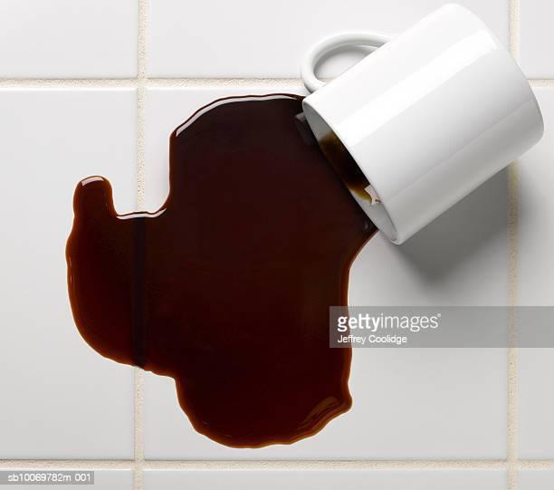 Spilled cup of coffee on tile floor, studio shot