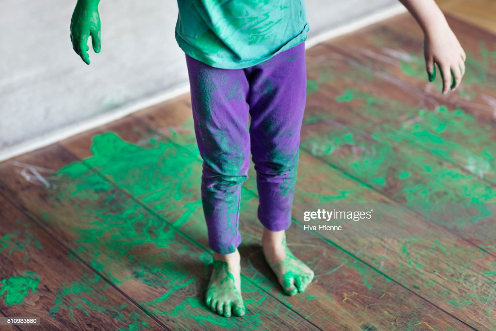 Spilled green paint on a child and wooden floor : Stock Photo