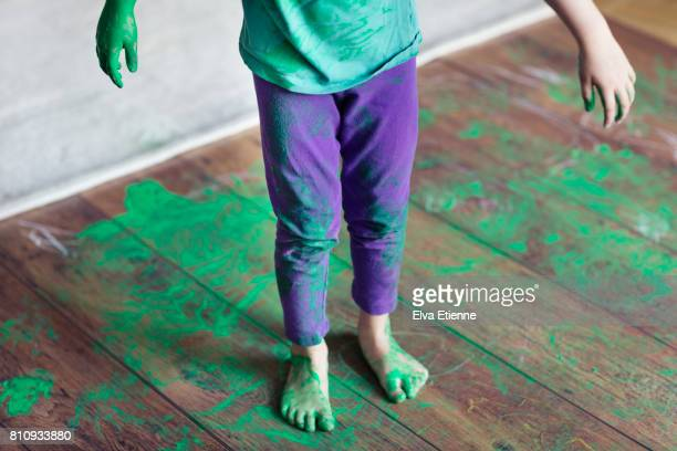 Spilled green paint on a child and wooden floor
