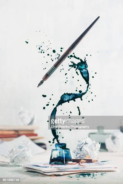 Spilled ink flying above inkwell in a spiraling splash with tiny drops and flying pen on a light background. Still life with writer workplace. Creative writing concept.